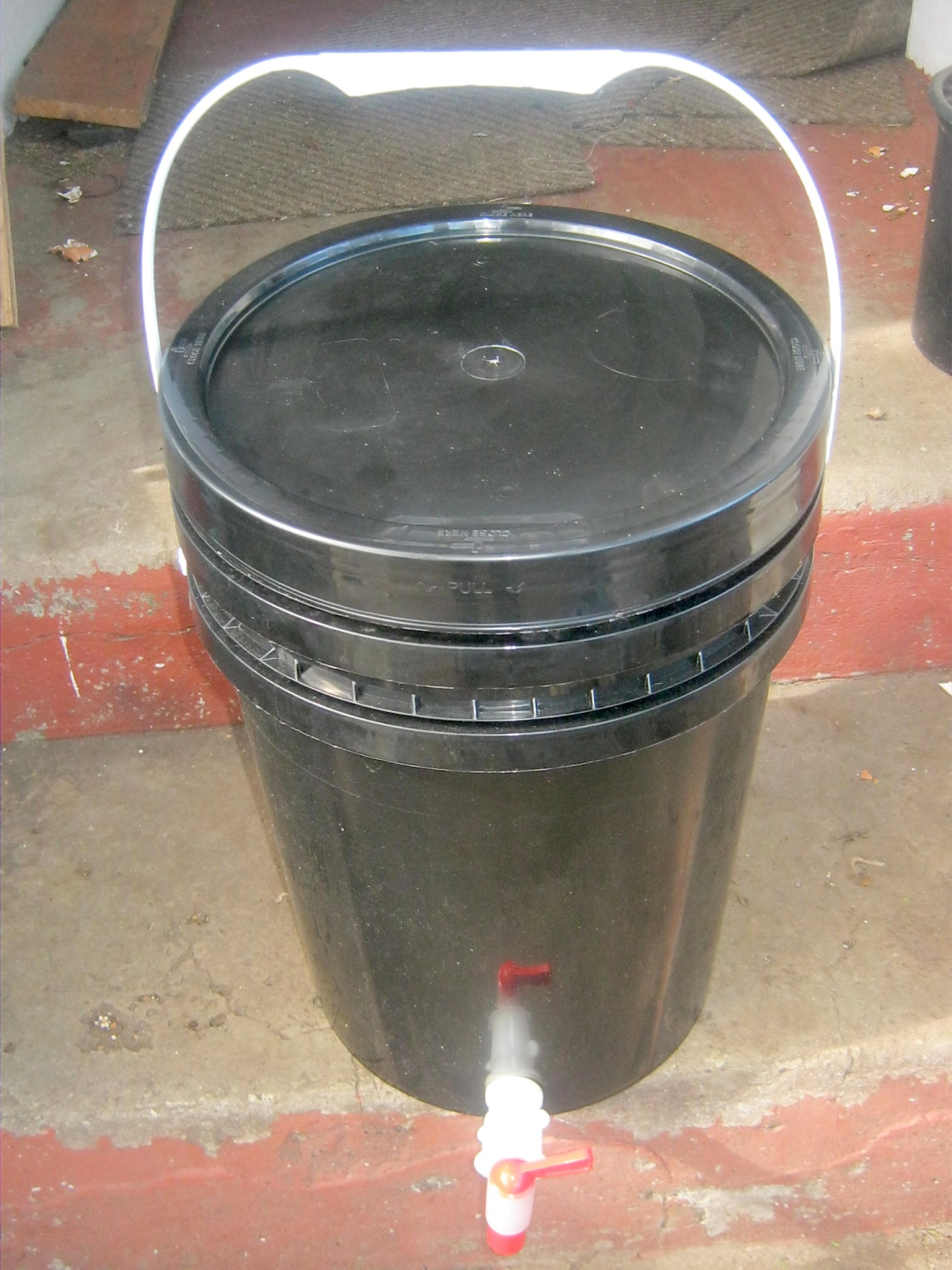 Two bin worm farm with drainage container, air holes, lid and tap to release worm tea and extra liquids.