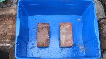 2 Ziegelsteine in einem wasserdichtem Container als Standplatz für eine Wurmfarm.